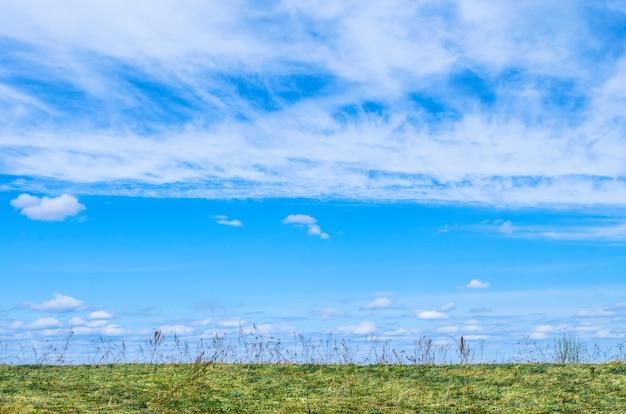 Blauer himmel und weißer zirrus, zirrusartige wolken unter dem feld und gras.