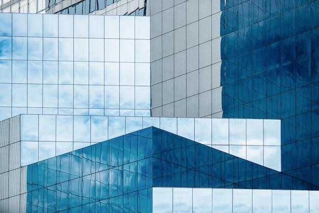 Blauer himmel und wolken, die in den fenstern des modernen bürogebäudes sich reflektieren