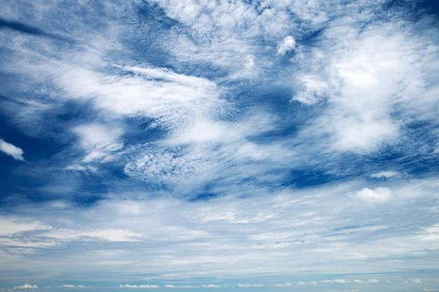 Blauer himmelhintergrund mit winzigen wolken