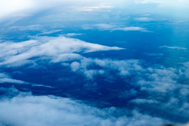 Blauer himmelshintergrund mit weißen wolken puffy clouds horizont blick aus dem flugzeugfenster nature