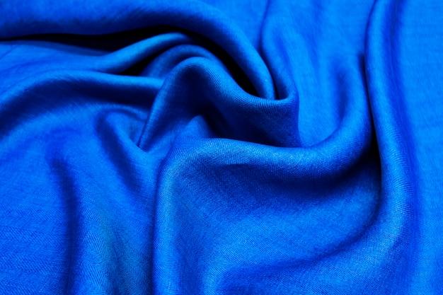Blauer hintergrund aus leinenstoff-denim. faltige weiche leinenblaue stoffstruktur.