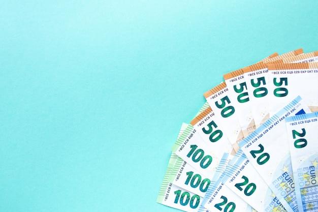 Blauer hintergrund. banknoten in stückelungen von 100, 50 und 20 euro mit linker ecke. das konzept von geld und finanzen. mit platz für text.