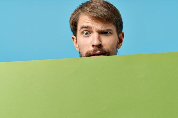 Blauer hintergrund des grünen banners des emotionalen bärtigen mannes