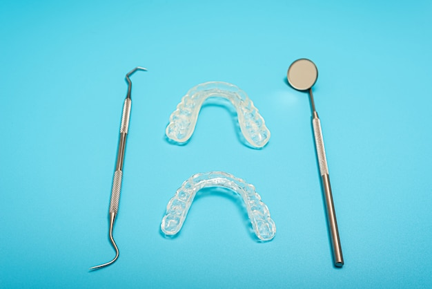 Blauer hintergrund für zahnkliniken mit zahnausrichtung und montageschienen, kopierraum.