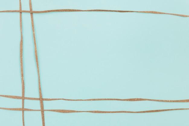 Blauer hintergrund mit braunen papierstreifen verziert