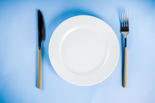 Blauer hintergrund mit einer platte, einer gabel und einem messer, draufsichtkopienraum