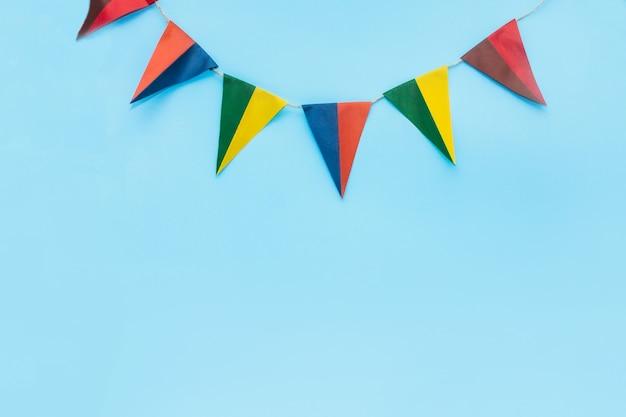 Blauer hintergrund mit flaggen, mehrfarbige dreieckige flaggen hängen oben, es gibt platz für text, vorderansicht
