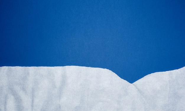 Blauer hintergrund mit weiß zerknitterte heftige papierelemente