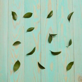 Blauer hölzerner hintergrund verziert mit flachen blättern der blätter
