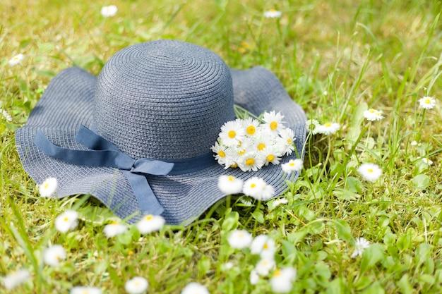 Blauer hut, der am sonnigen tag auf einem grünen gras mit kleinem gänseblümchenblumenstrauß liegt. blumenstrauß aus wiese und wildblumen. romantisches foto einer süßen sommerzeit. urlaubskonzept