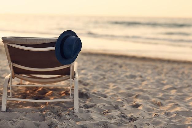 Blauer hut, der auf einem liegestuhl am strand liegt