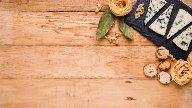 Blauer käse; brot; pasta und lorbeerblätter auf schwarzem stein über arbeitsplatte mit platz für text