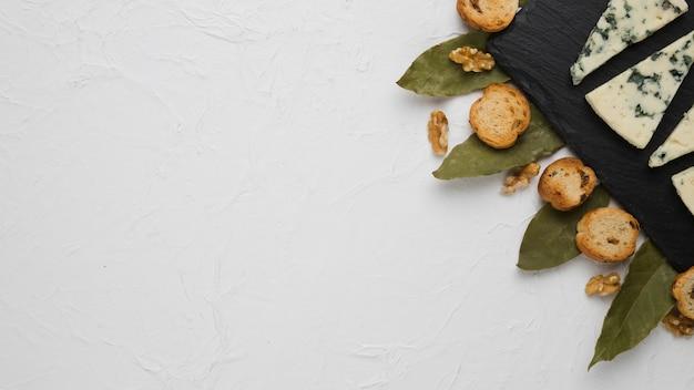 Blauer käse; brotscheibe; walnuss- und lorbeerblätter mit kopienraumhintergrund