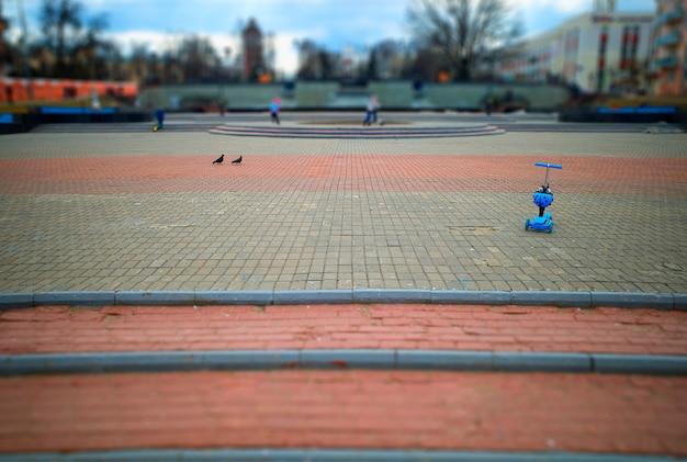 Blauer kinderpedalzyklus-stadthintergrund