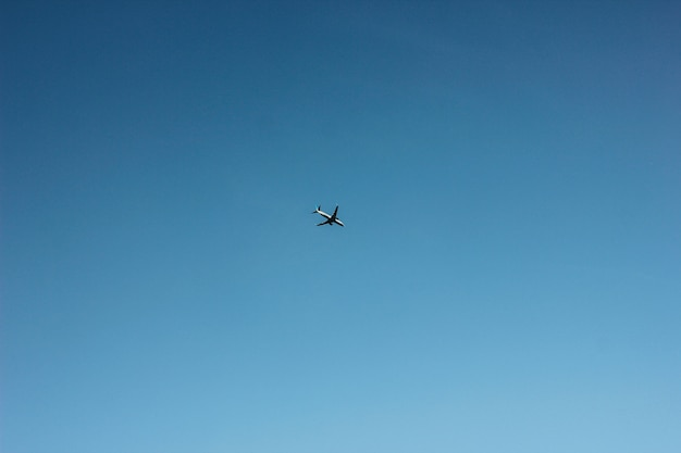 Blauer klarer himmel mit fliegendem flugzeug, hintergrund