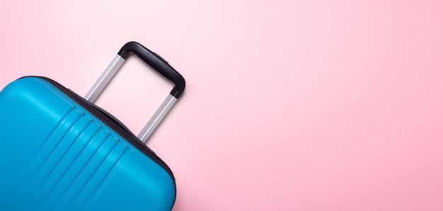 Blauer koffer auf pastellrosahintergrund kreative sommerferien, ferien, reisekonzept