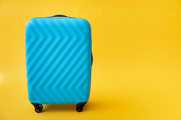 Blauer koffer gegen gelbe wand. sommerferien- und reisekonzept