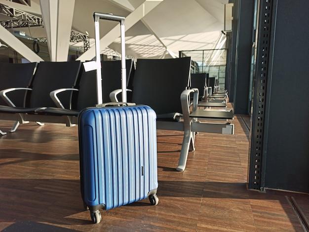 Blauer koffer im leeren flughafen