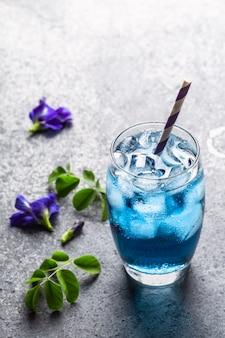 Blauer kräutertee der schmetterlingserbsenblume auf grauem beton.