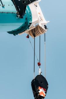 Blauer kranhubmechanismus mit haken in der nähe des modernen glasgebäudes, kran und hydraulischem hochhub bis zu 120 metern.