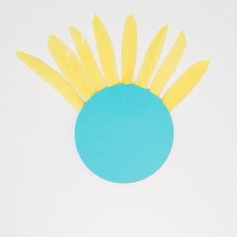 Blauer kreisrahmen mit gelben federn gegen weißen hintergrund