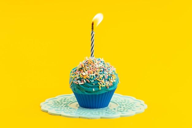 Blauer kuchen der vorderansicht mit bunten kleinen bonbons und kerze auf gelbem, gefärbtem kekszucker