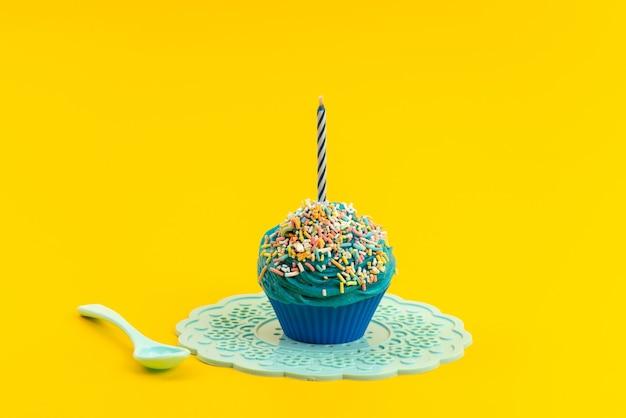 Blauer kuchen der vorderansicht mit kerzenweißem plastiklöffel auf gelber keks-süßwarenfarbe