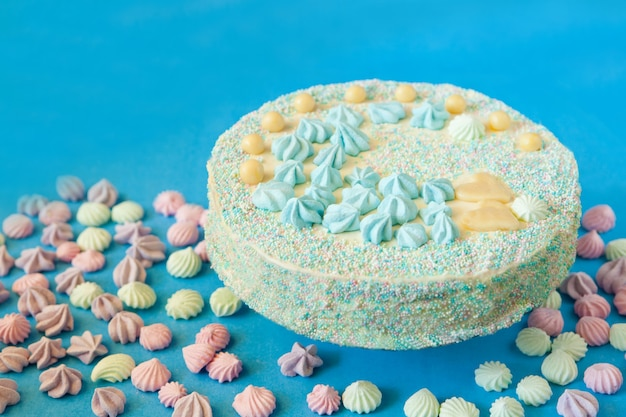 Blauer kuchen für babyparty-party mit baiser. hausgemachter kuchen für einen neugeborenen jungen auf blauem grund.