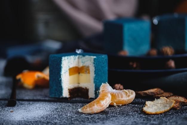 Blauer kuchen gefüllt mit orange und mandarine in form eines würfels. in der nähe auf einem schwarzen tisch sind zutaten orangen, mandarinen, nüsse. rustikaler stil