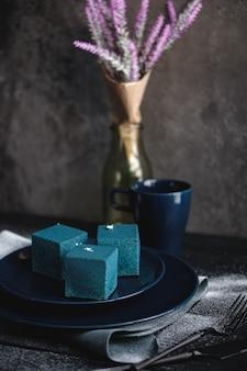 Blauer kuchen in form eines würfels. rustikaler stil.