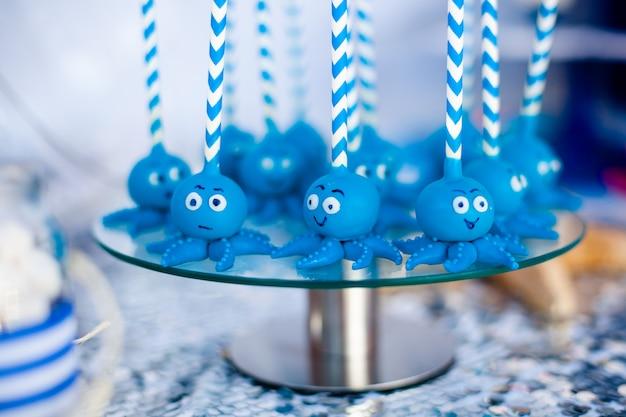 Blauer kuchen knallt die lustigen kraken, die auf der runden glasplatte geteilt werden.