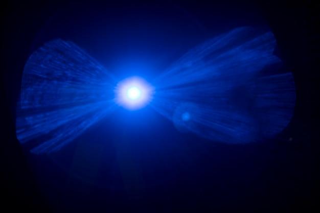 Blauer lens flare-effekt auf einem schwarzen hintergrundbild