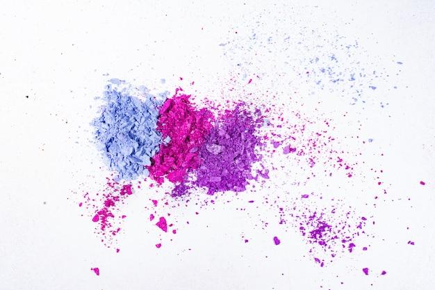 Blauer, lila und rosa zerquetschter lidschatten lokalisiert auf weißer oberfläche