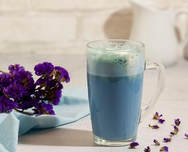 Blauer matcha-tee in einem glas latte auf dem tisch.