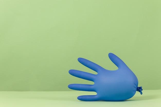 Blauer medizinischer handschuh aufgeblasen wie luftballons auf einem grünen hintergrund