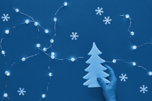 Blauer monochromer weihnachtshintergrund. hand, die keramik-tannenbaumdekoration hält. neujahrs- oder weihnachtswohnung lag. weihnachtsferien. draufsicht, papierschneeflocken und girlande der lichter auf papierhintergrund.