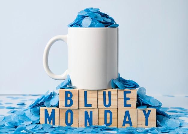 Blauer montag mit becher und papierregen