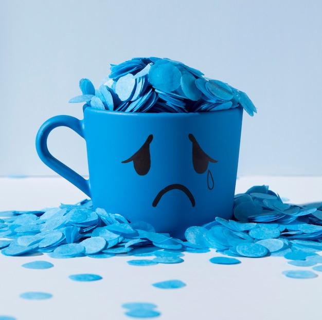 Blauer montag mit papierregen und tränenreichem becher