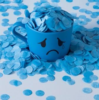 Blauer montag mit papierregen und weinendem becher