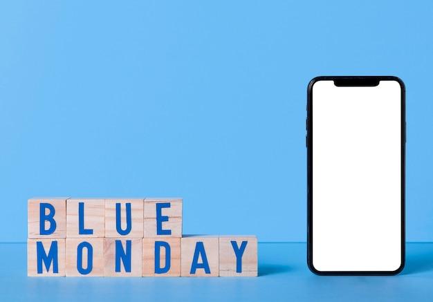 Blauer montag mit smartphone und holzwürfeln