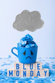 Blauer montag mit tränenreichem becher und holzwürfeln