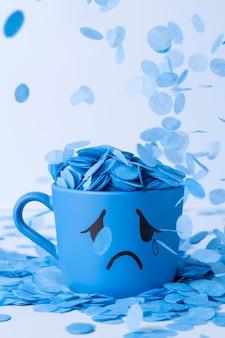 Blauer montag mit weinendem becher und papierregen