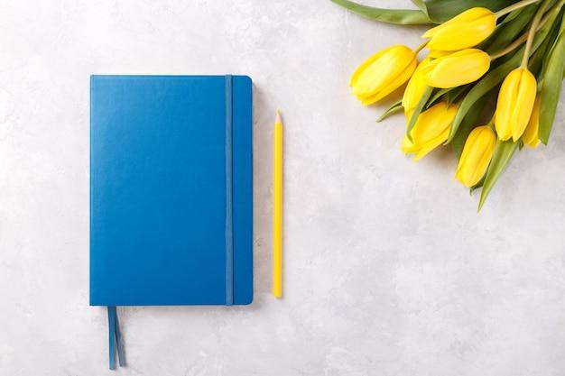 Blauer notizblock und tulpenhintergrund