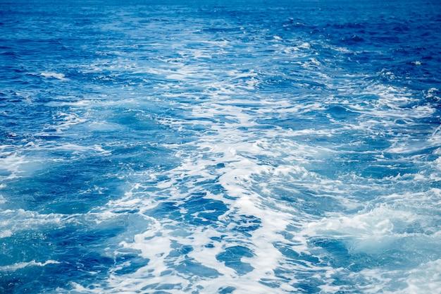 Blauer oberflächenhintergrund mit dem spritzen von wellen