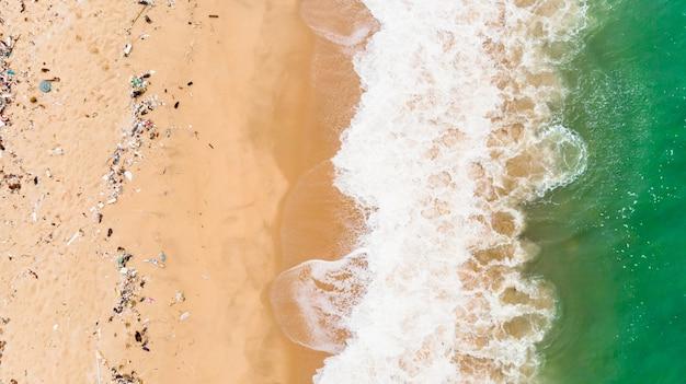 Blauer ozean am sandigen strand mit plastikmüll und medizinischem abfallmaterial im tropischen strand der andamanensee