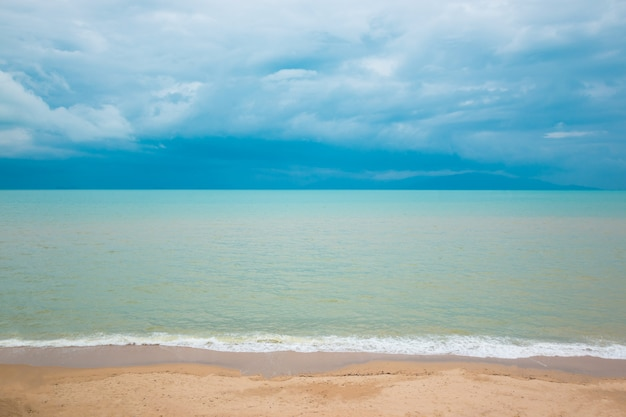 Blauer ozean und sandstrand unter bewölktem himmel