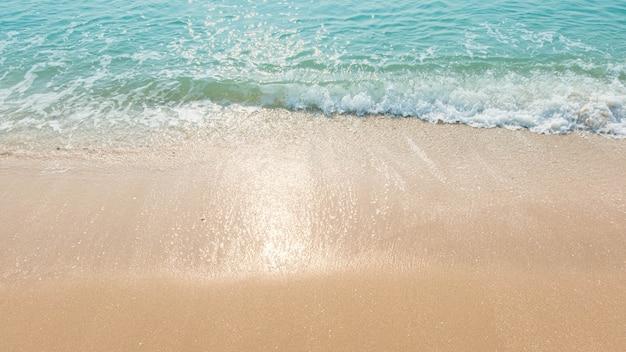 Blauer ozeanwellen sonnenlichtreflexionssandstrandhintergrund