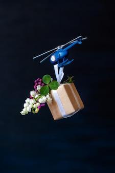 Blauer papierbox-geschenkspielzeuglieferhubschrauberblumenschwarzer hintergrund