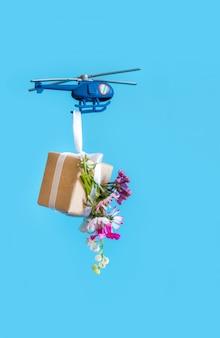 Blauer papierkastengeschenkspielzeuglieferhubschrauberblumenhintergrund