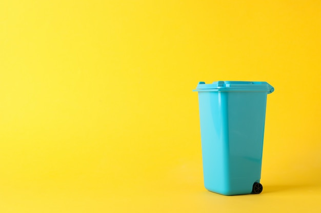 Blauer papierkorb auf gelbem hintergrund, platz für text